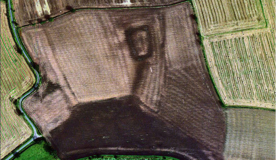 Figure 4: Woodhouse field moat in 1999 (dark rectangle at top middle of frame).  Ridge and furrow patterns and the dark outline of the moat are now visible as soil marks in this recently ploughed field
